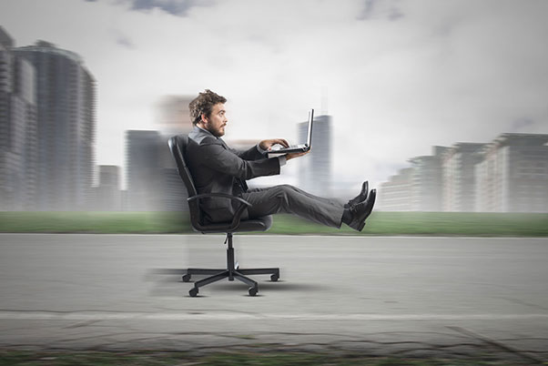 man on office chair going fast